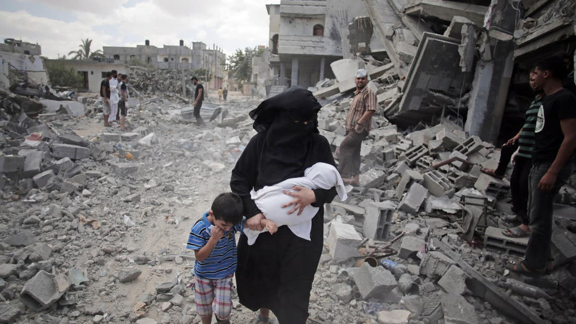 In this Aug. 4, 2014 file photo, a Palestinian woman passes by rescuers inspecting the rubble of destroyed houses following Israeli strikes in Rafah refugee camp, southern Gaza Strip. (AP)