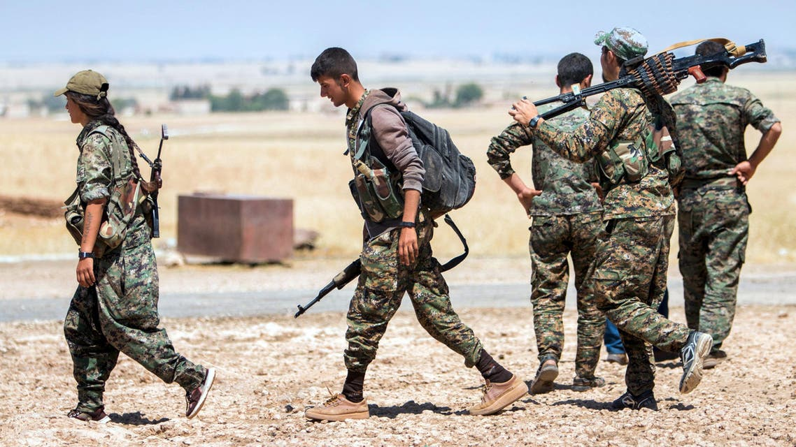 Kurdish People's Protection Units fighters walk with their weapons at the eastern entrances to the town of Tal Abyad in the northern Raqqa countryside, Syria