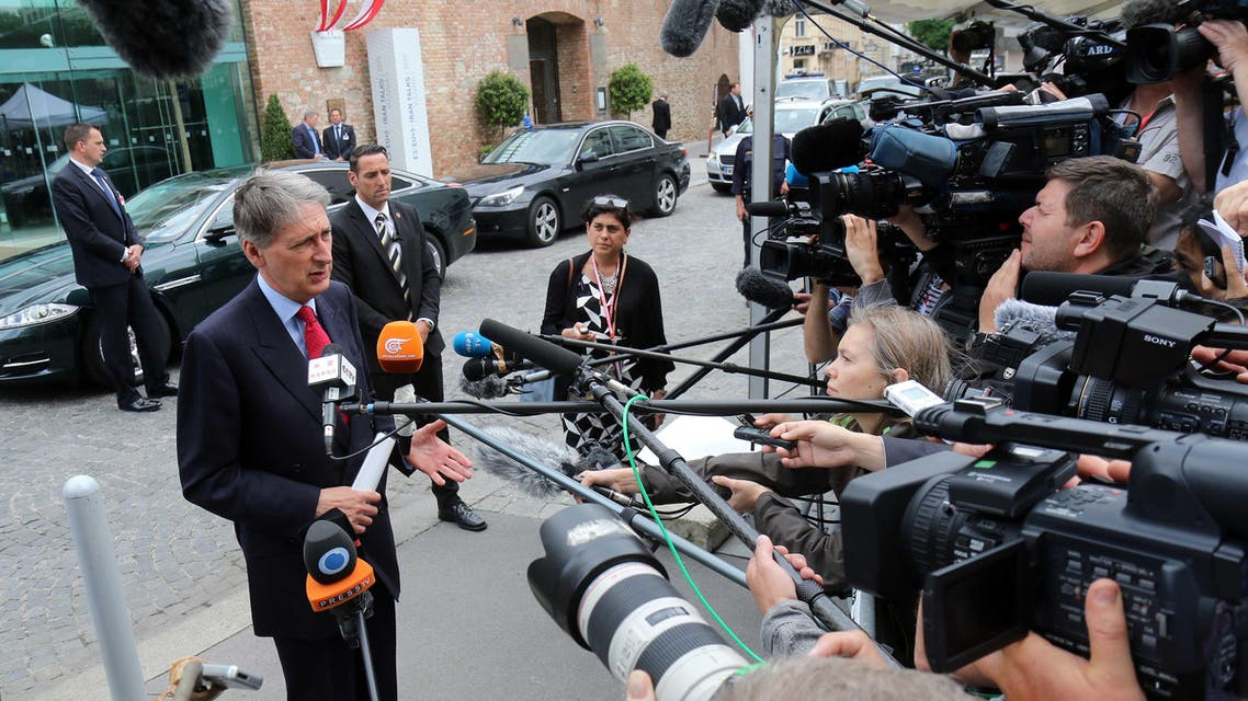 Britain's Foreign Secretary Philip Hammond, left, talks to media as he arrives at the Palais Coburg where closed-door nuclear talks with Iran take place in Vienna, Austria, Sunday, June 28, 2015.