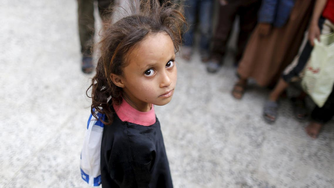 A girl waits for her family's ration at a food assistance center run by volunteers in Sanaa. AP
