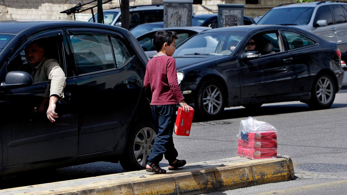 A Syrian street vendor, who fled his home in Syria, sells tissues in Beirut, Lebanon, Wednesday, April 15, 2015