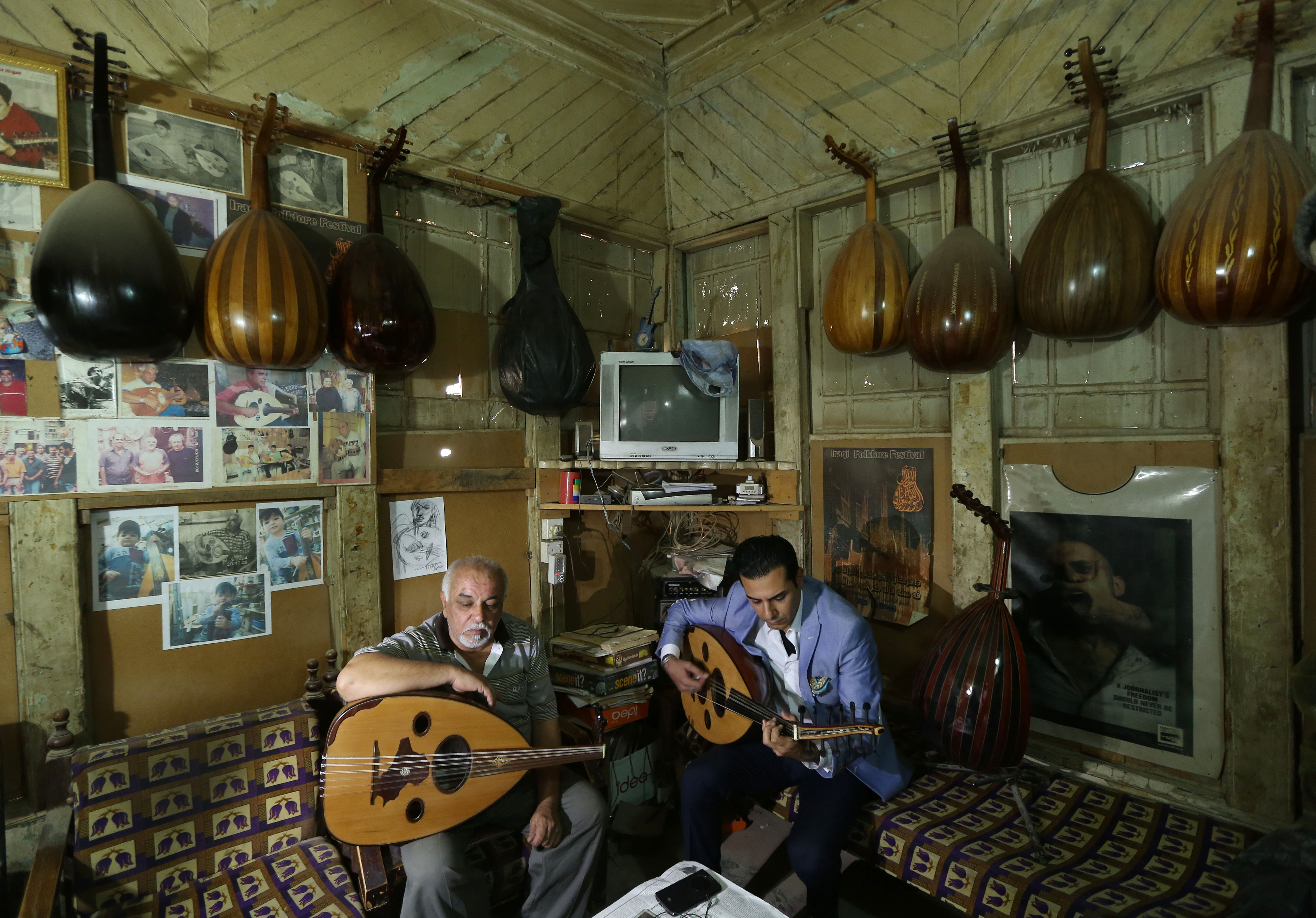 In this photo taken Thursday, June 18, 2015, Bassam Salim, right, and Mahmoud Abdulnabi , left, play on ouds at Abdulnabi's workshop in Baghdad, Iraq. The Islamic State group has banned music in the third of Iraq under its control, but in Baghdad a growing number of musicians and other artists are defying the extremists, hoping to revive a rich culture smothered by decades of war. (AP Photo/Hadi Mizban)