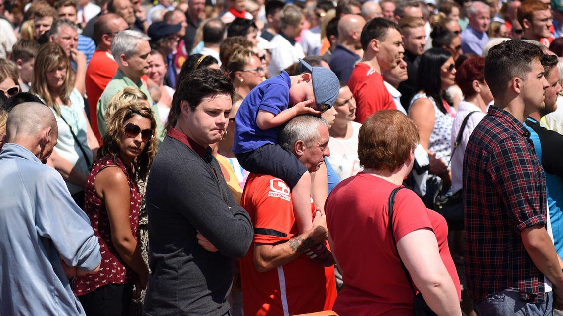 Members of the public observe a minute's silence for the victims of the Tunisia attacks outside Walsall football club in central England, on July 3, 2015. AFP
