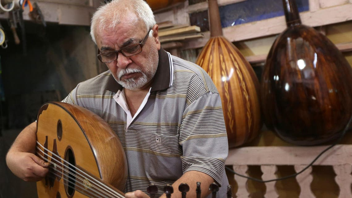 """In this photo taken Saturday, June 20, 2015, Mahmoud Abdulnabi tries out an oud, an Arabic instrument related to the lute, at his workshop in Baghdad, Iraq. """"The oud is different than other musical instruments,"""" said Abdulnabi, who has crafted ouds played by some of Iraq's best known musicians, many of whom look down from headshots on the walls. """"If you feel joyful, it can play your joy. If the circumstances are sad it can play your sorrow and... help to empty whatever is in your chest."""" (AP Photo/Hadi Mizban)"""