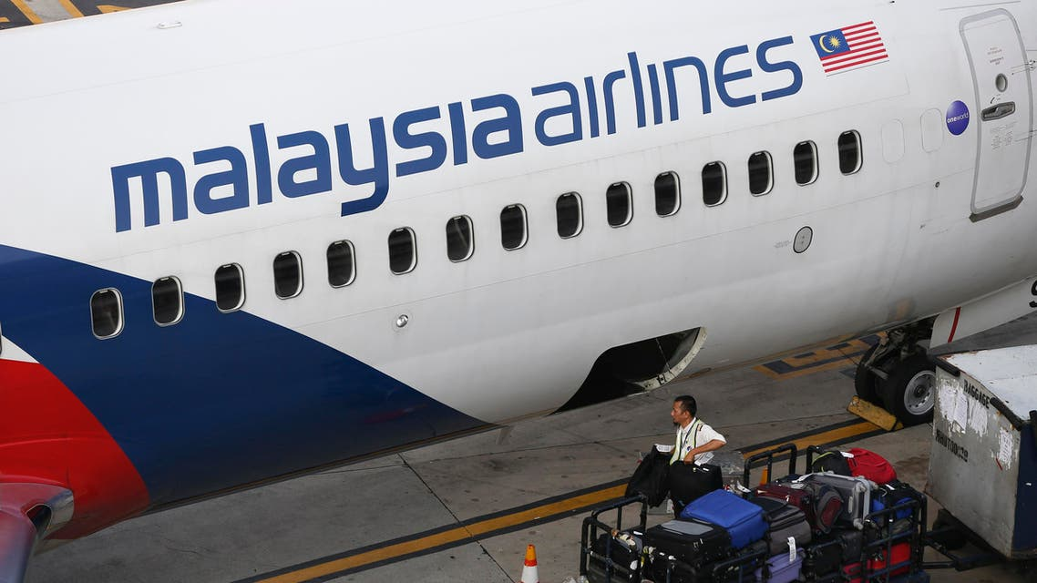 A Malaysia Airlines ground staff member unloads luggage from a plane at Kuala Lumpur International Airport in Sepang, Malaysia Monday, June 1, 2015. The new CEO of Malaysia Airlines said the ailing carrier could break even by 2018 after cutting staff, selling surplus aircraft and refurbishing its international fleet. (AP Photo/Vincent Thian)