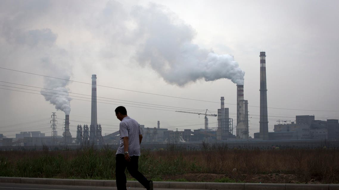 In this May 29, 2015 photo, a man walks past a coal-powered steel plant in Tianjin, China.  (AP)
