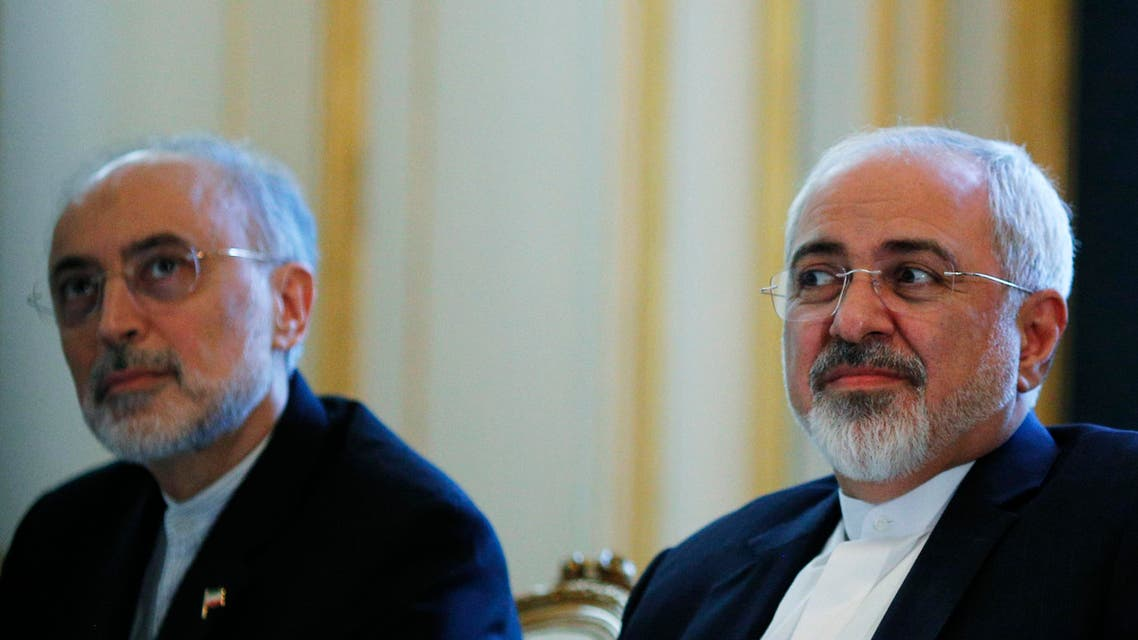 "Iranian Foreign Minister Mohammad Javad Zarif and the Head of the Iranian Atomic Energy Organization Ali Akbar Salehi, left, meet with U.S. Secretary of State John Kerry in Vienna, Austria, Friday July 3, 2015. Iran has committed to implementing the IAEA's ""additional protocol"" for inspections and monitoring as part of an accord, but the rules don't guarantee international monitors can enter any facility including sensitive military sites, so making it difficult to investigate allegations of secret work on nuclear weapons. (Carlos Barria/Pool via AP)"