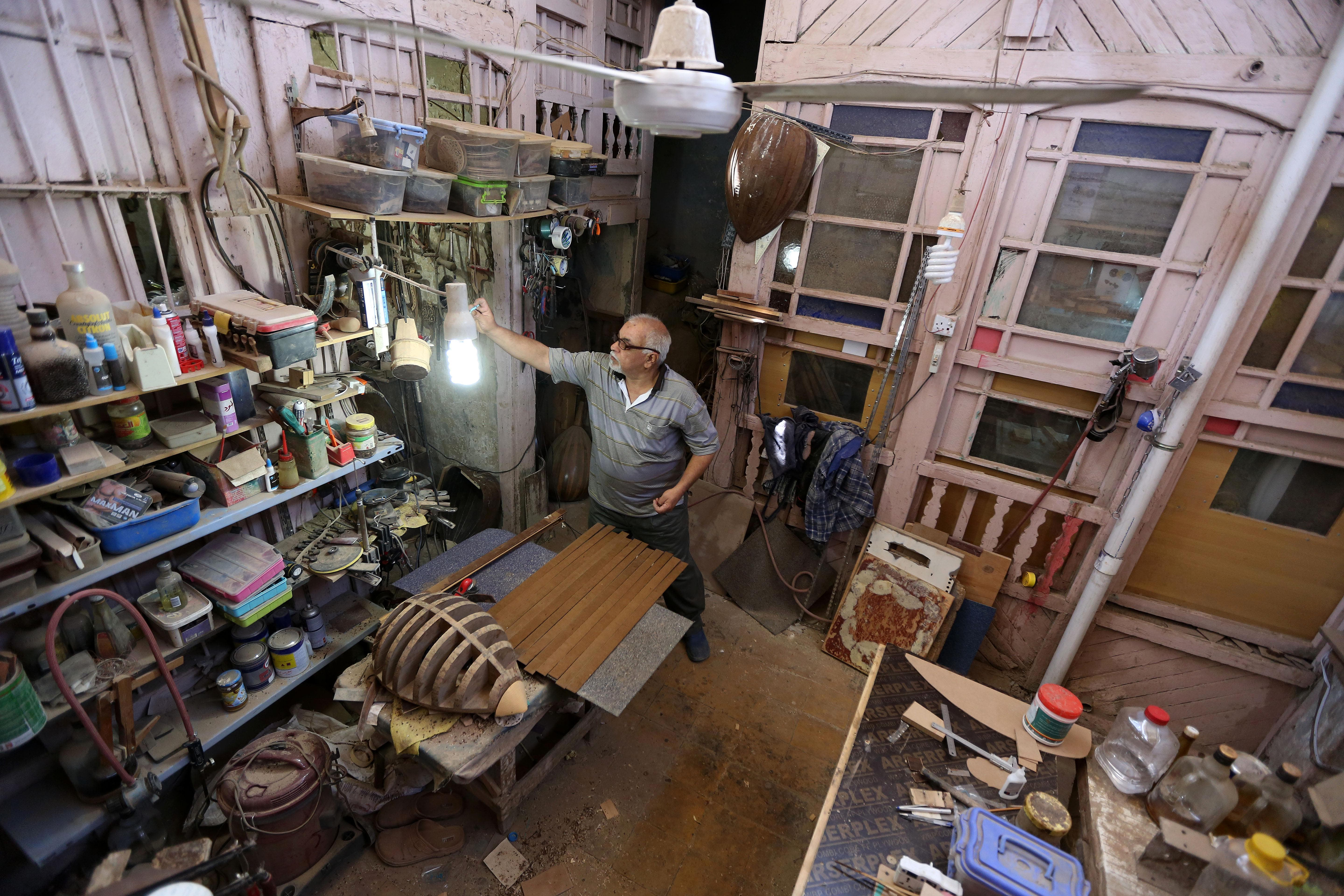 """In this photo taken Thursday, June 18, 2015, Oud maker Mahmoud Abdulnabi works in his shop in Baghdad, Iraq. Abdulnabi is one of the last craftsmen in Baghdad who carves ouds by hand. """"Our brothers, the makers in Syria, Turkey and Egypt, might produce 12 pieces a day"""" using machines, Abdulnabi said. """"We produce one or two pieces in a month."""" (AP Photo/Hadi Mizban)"""