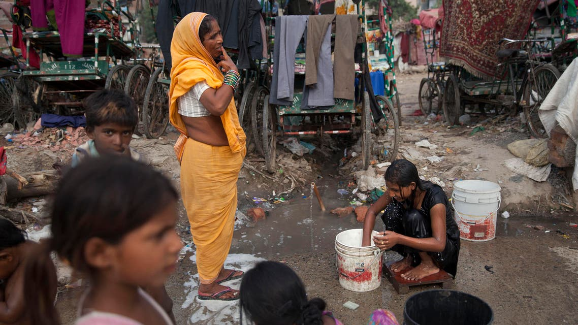 An Indian girl bathes beside a woman brushing her teeth at a shanty area in New Delhi, India, Tuesday, June 30, 2015. There is no direct supply of potable water at homes in most of the poor neighborhoods in the country and people have to depend on regulated supply of water from public taps erected on roadsides, with a single tap catering to hundreds of households. (AP Photo/Tsering Topgyal)