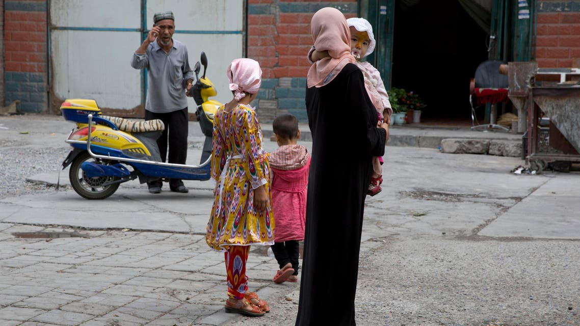 In this photo taken Thursday, July 17, 2014, a Uighur woman wears a full length garment and headscarf associated with conservative Islam in the city of Aksu in western China's Xinjiang province. AP