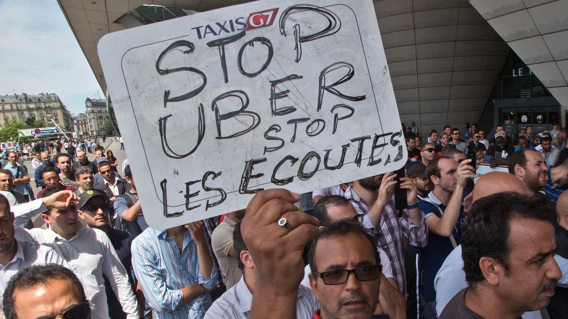 """A striking taxi driver holds a placard which read, """"Stop Uber, Stop listening,"""" referring to the new US spying report in France, during a taxi drivers demonstration in Paris, France, Thursday, June 25, 2015."""