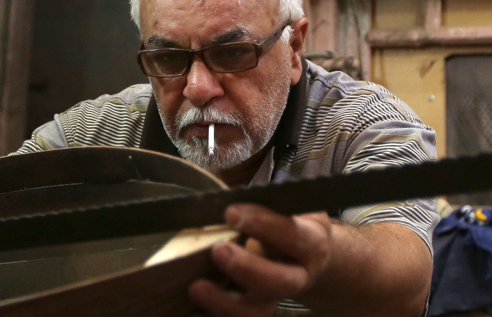 In this photo taken Saturday, June 20, 2015, Mahmoud Abdulnabi works on an oud, an Arabic instrument related to the lute, at his workshop in Baghdad, Iraq.(AP Photo/Hadi Mizban)