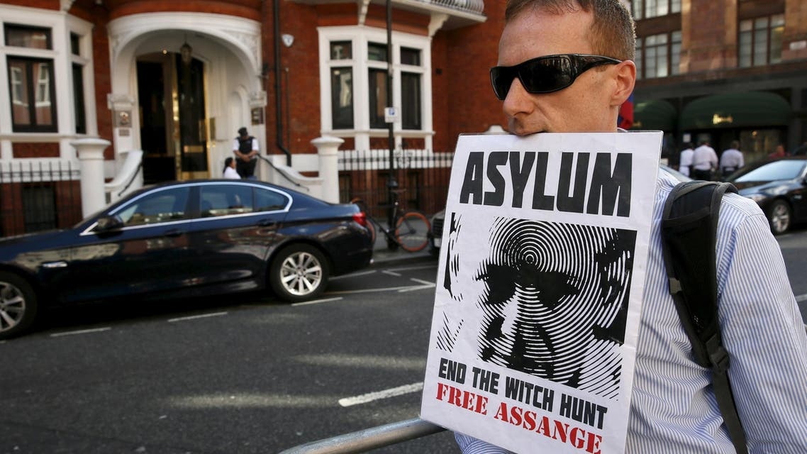A supporter of Wikileaks founder Julian Assange holds a placard with his mouth during a gathering outside the Ecuador embassy in London, Britain June 19, 2015. (Reuters)