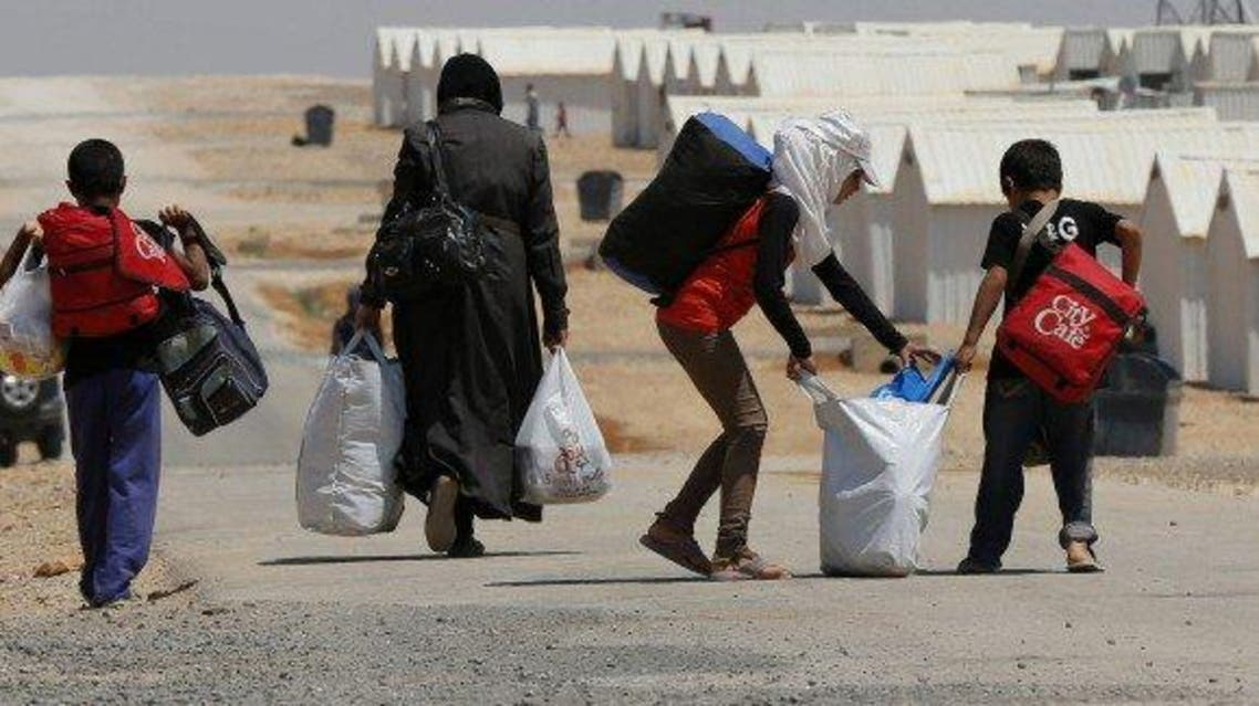 Image: Newly-arrived Syrian refugees carry their belongings as they walk at Azraq refugee camp near Al Azraq area, east of Amman, August 19, 2014. REUTERS/Muhammad Hamed