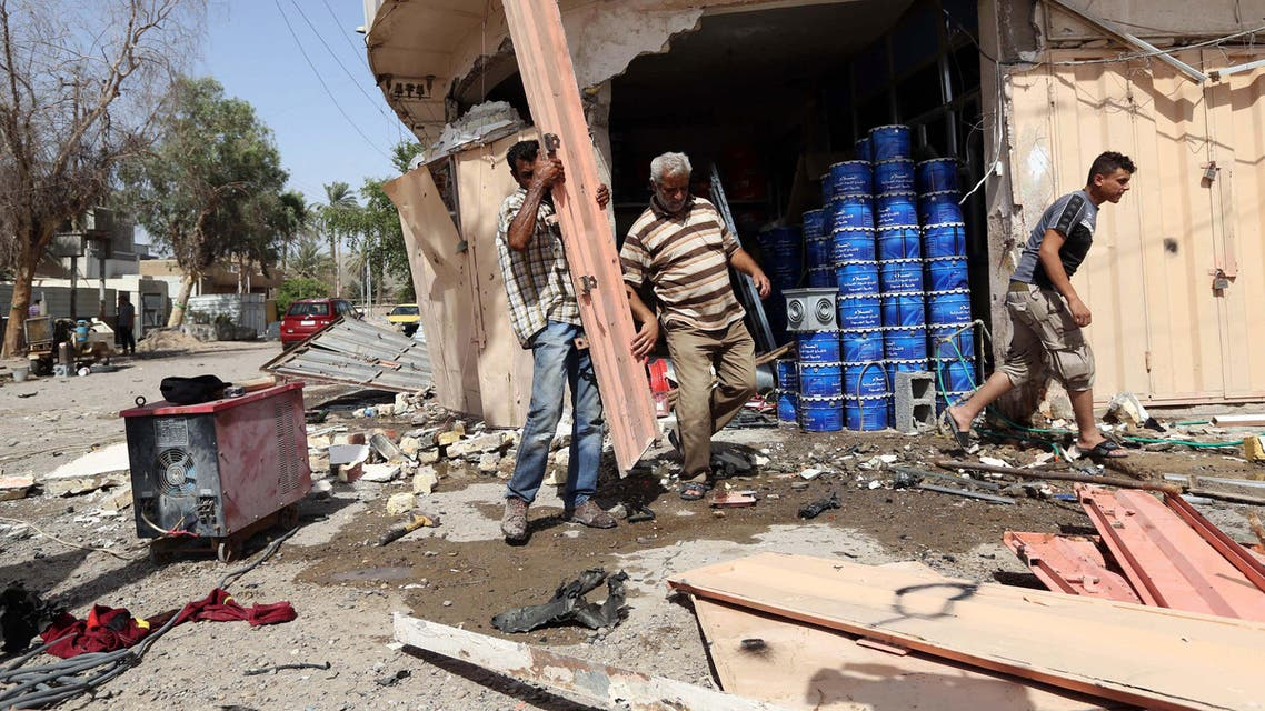 Civilians pass by the site of a car bomb attack in Baghdad's northern neighborhood of Shaab, Iraq, Thursday, June 25, 2015. AP