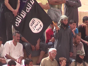 A man waves an ISIS flag as the crowd look on (Video grab)
