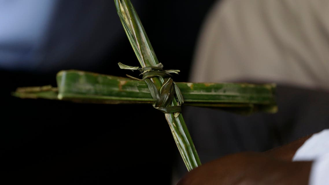 A Nigerian holds a cross made out of a palm leaf, during Palm Sunday mass at St Theresa's Catholic Church, in Yola, Nigeria. Sunday, March 29, 2015. (AP Photo/Sunday Alamba)