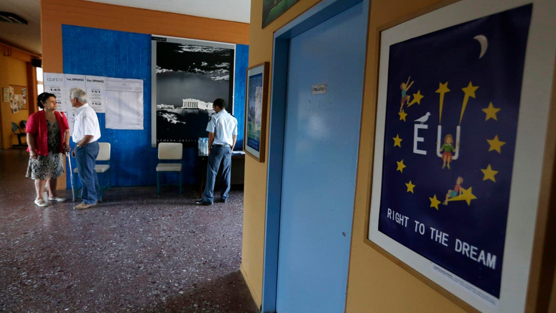 A couple arrives to vote as a policeman stands under Acropolis photograph at a polling station in Athens, Sunday, July 5, 2015.