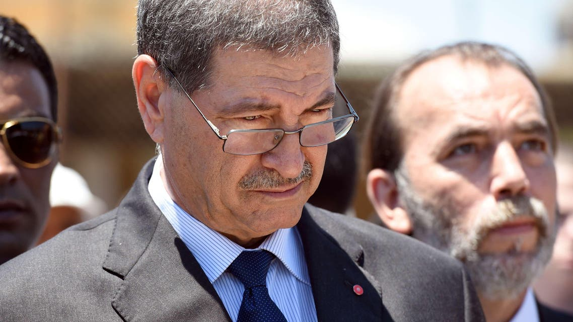 Tunisian Prime Minister Habib Essid observes a minute's silence on the beach in the Tunisian coastal city of Sousse on July 3, 2015. AFP