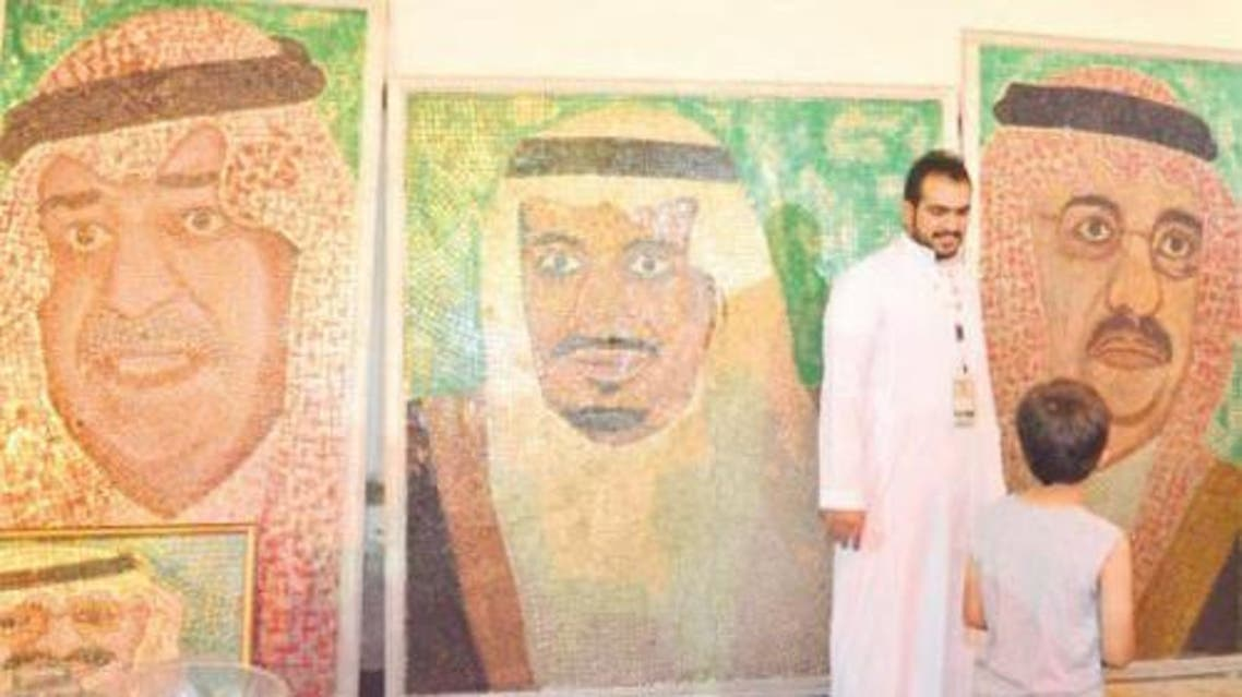 Hisham Abdu Rabbah Al-Najjar standing by his portraits at the heritage festival in Balad. — SG photo