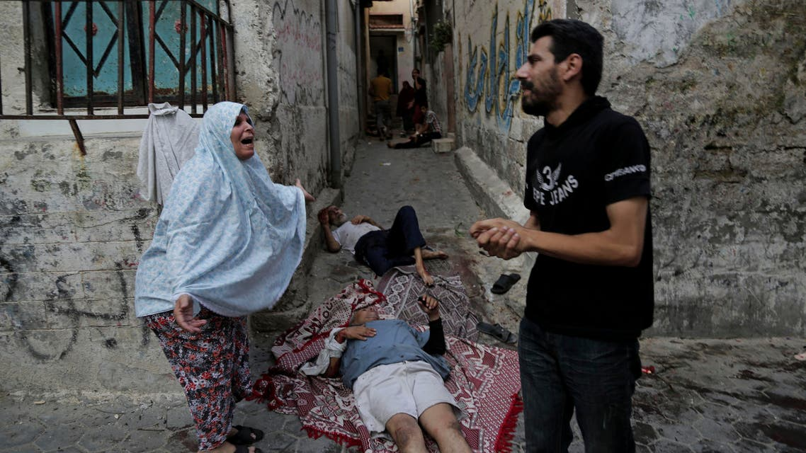 In this July 30, 2014 file photo, a Palestinian woman reacts while standing next to two injured men as they lay on the ground and wait for help following an Israeli strike in the Shijaiyah neighborhood of Gaza City. (AP)