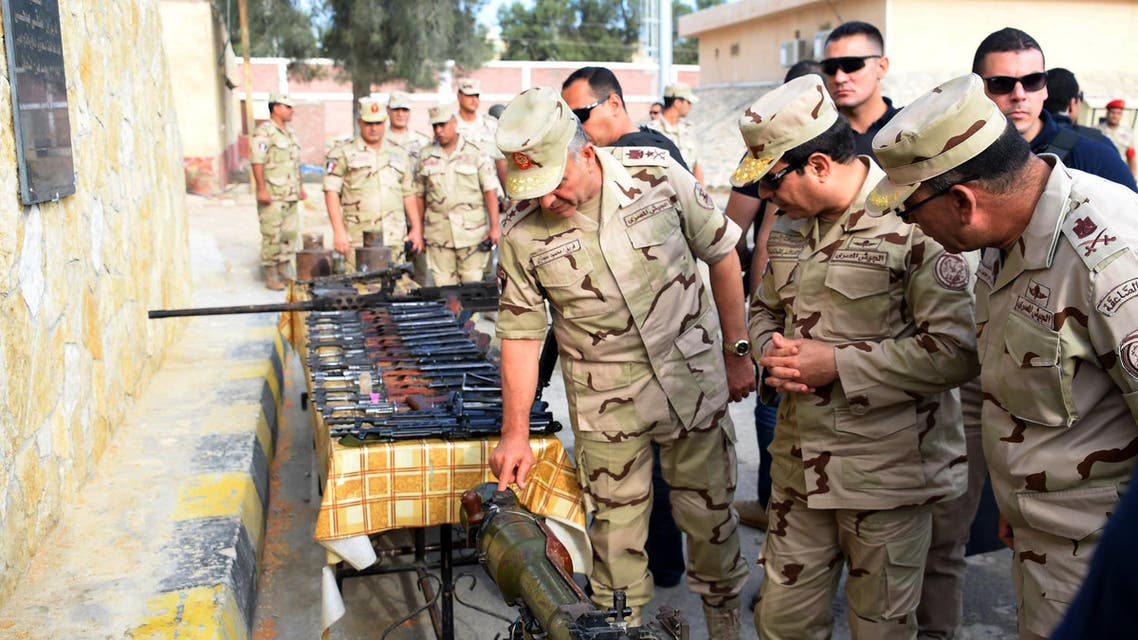 In this picture provided by the office of the Egyptian Presidency, Egyptian President Abdel-Fattah el-Sissi, second right, inspects weapons with members of the Egyptian armed forces in Northern Sinai, Egypt, Saturday, July 4, 2015. Egyptian President Abdel-Fattah el-Sissi has traveled to the troubled northern part of the Sinai Peninsula to inspect troops, after Islamic State-linked militants struck a deadly blow against the military this week in a coordinated assault. (Egyptian Presidency /Mohammed Abdel-Muati via AP)