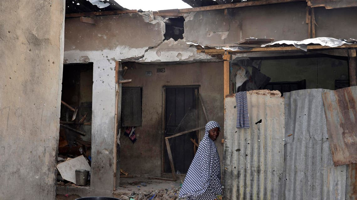A girl walks past a house damaged in Saturday's rocket propelled grenades by Islamic extremist in Maiduguri, Nigeria, Sunday, May 31, 2015. A bomb injured four people in a market Sunday in Maiduguri, a day after the northeastern Nigerian city was hit by a suicide bomber who killed 16 in a mosque. (AP Photo/Jossy Ola)