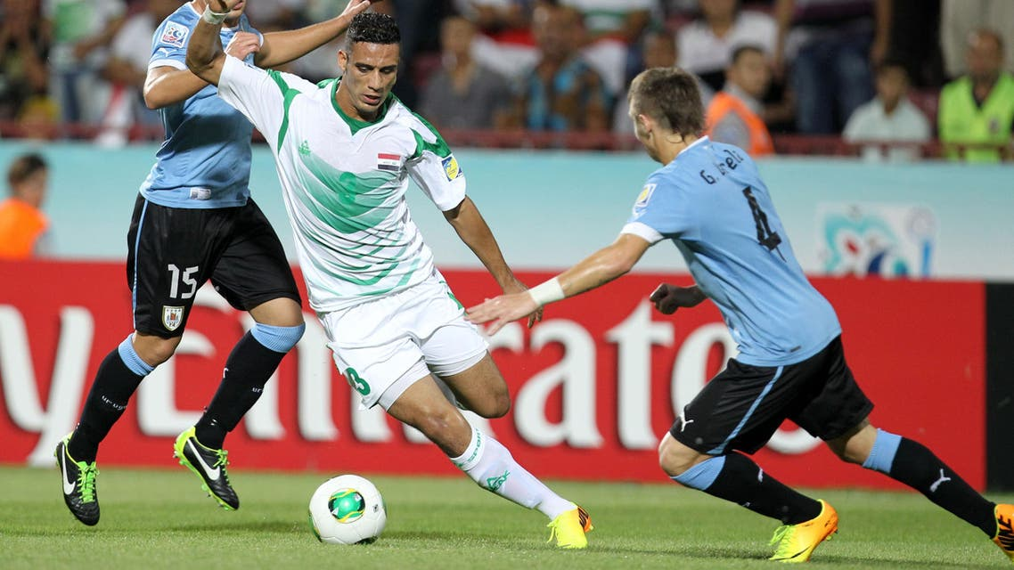 Iraq's Ali Adnan, center, dribbles between Uruguay's Guilermo Varela, right, and Gino Acevedo, during their Under-20 World Cup semifinal soccer match at the Huseyin Avni Aker stadium in Trabzon, Turkey, Wednesday, July 10, 2013. (AP Photo/Thanassis Stavrakis)