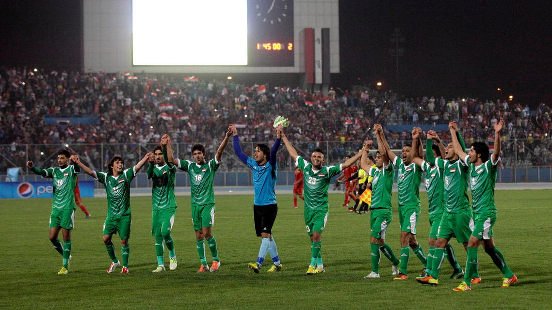 Iraq's national football team celebrates after an international friendly soccer match between Iraq and Syria in Baghdad, Tuesday, March 26, 2013. Tens of thousands of Iraqi football fans packed a stadium in eastern Baghdad on Tuesday to watch the country's first international match at home for 18 months, a 2-1 victory over Syria. (AP Photo/ Khalid Mohammed)