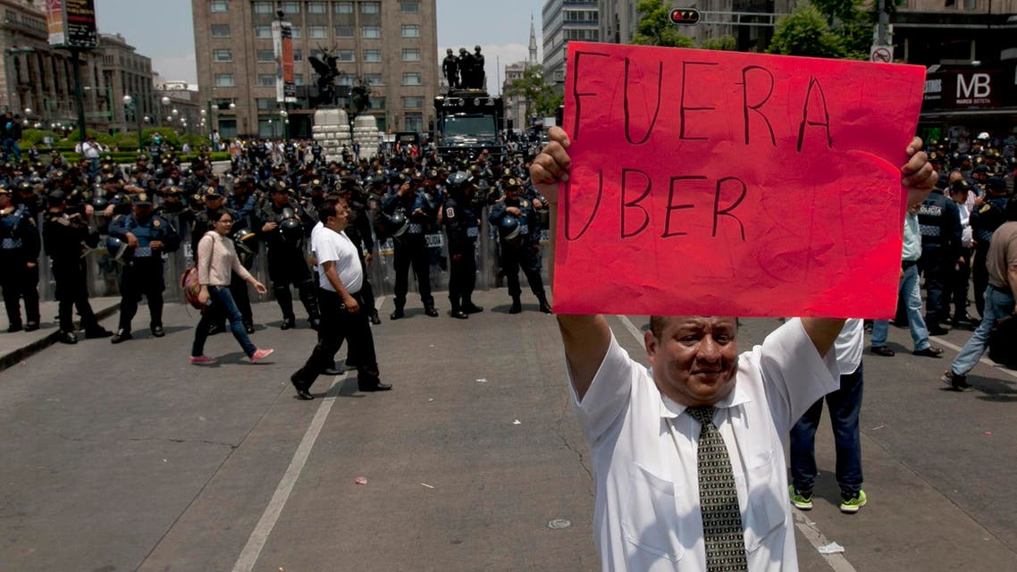 """A man holds a sign that reads in Spanish """"Uber Out"""" in front of a line of riot police as thousands of taxi drivers blocked the main streets to protests against Uber in Mexico City. (File Photo: AP)"""