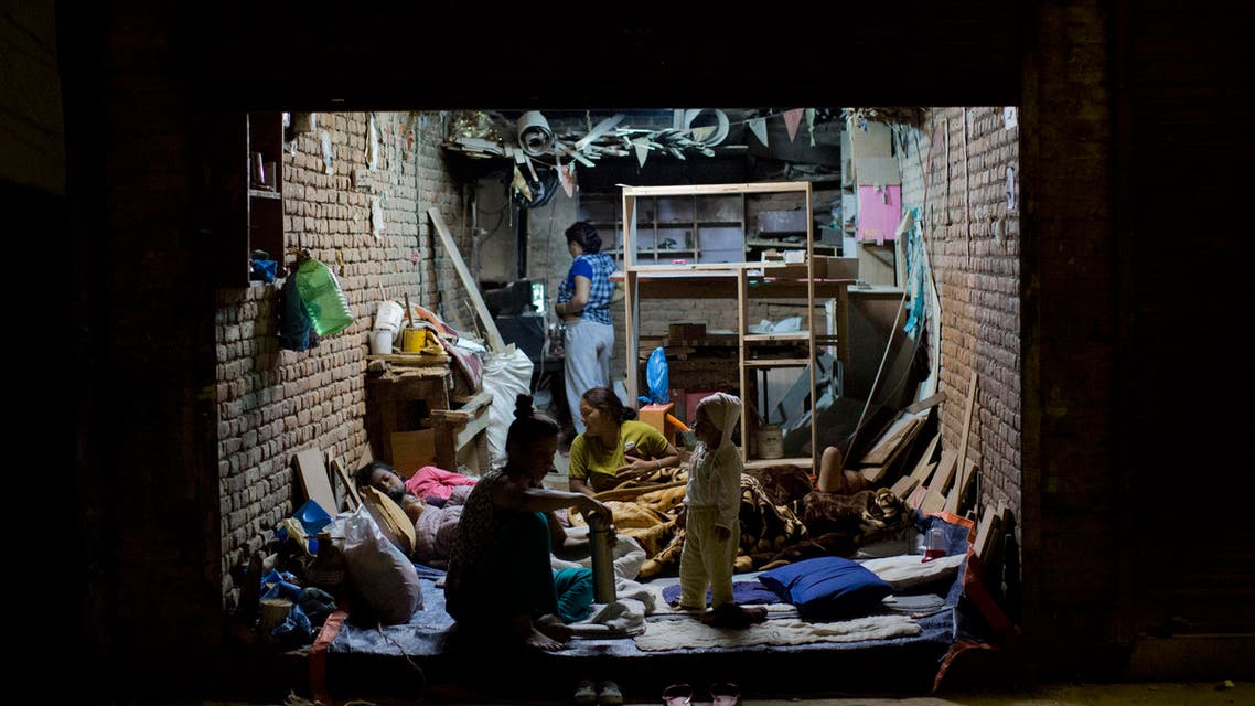 A family gathers on the ground level of their house to rest for the night in Kathmandu, Nepal, Tuesday, May 12, 2015.