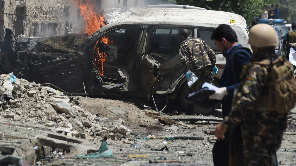 Afghan security forces inspects the damaged vehicle at the site of a suicide bomber that targeted NATO forces in Kabul on July 7, 2015. (AFP)