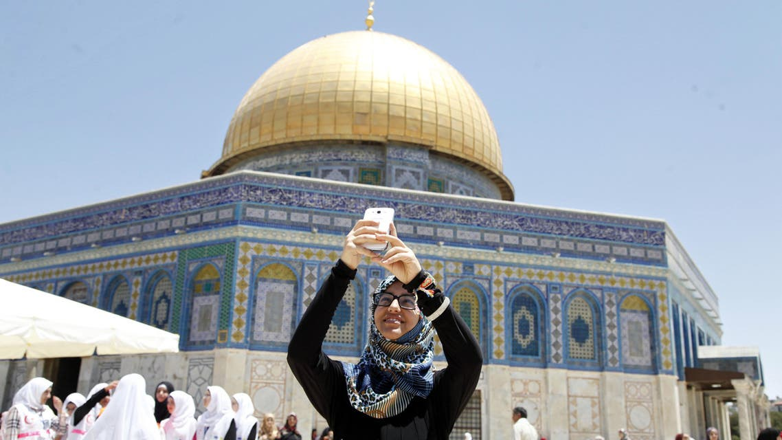 A Palestinian woman takes a photo next to the Dome of the Rock Mosque in the Al Aqsa Mosque compound, on the third Friday of the Muslim holy month of Ramadan, in Jerusalem's old city, Friday, July 3, 2015.