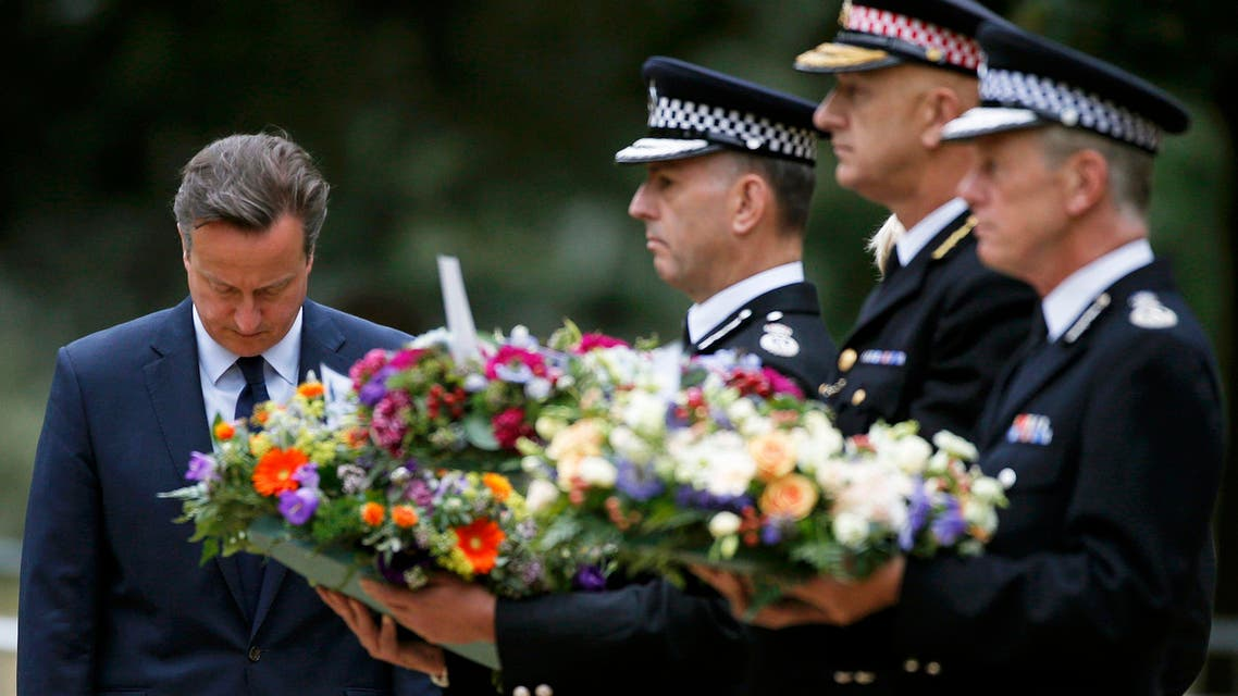 Britain's Prime Minister David Cameron bows as he stands with police officers after laying a wreath at the memorial to victims of the July 7, 2005 London bombings, in Hyde Park, central London, Britain July 7, 2015. Britain fell silent on Tuesday to commemorate the 10th anniversary of attacks targeting London public transport which killed 56 people, the first suicide bombings by Islamist militants in western Europe. REUTERS/Peter Nicholls TPX IMAGES OF THE DAY