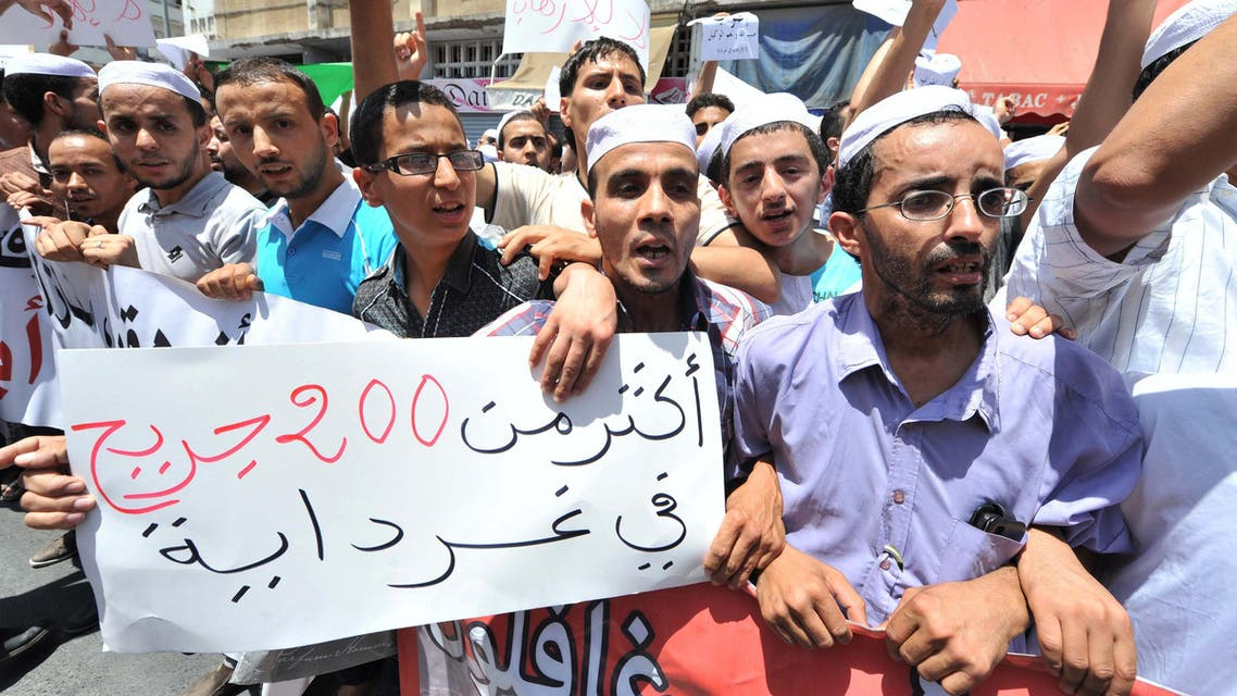 Hundreds of demonstrators of the Berber community stage a protest in front of a walled area where Algier's newspapers are headquartered in support of Berbers in the southern Ghardaia region where at least 22 people have died in ethnic unrest, in Algiers, Algeria, Wednesday, July 8, 2015. Authorities say ethnic clashes have left at least 22 people dead around Algeria's southern oasis city of Ghardaia, more than 600 kilometers (375 miles) south of Algiers, prompting the president to call an urgent security meeting. The Berbers and the Arabs in Ghardaia had for centuries lived together in harmony, but tensions started in late 2013 when a Berber shrine was vandalized. Poster reads in read : 200 wounded people. (AP Photo/Sidali Djarboub)