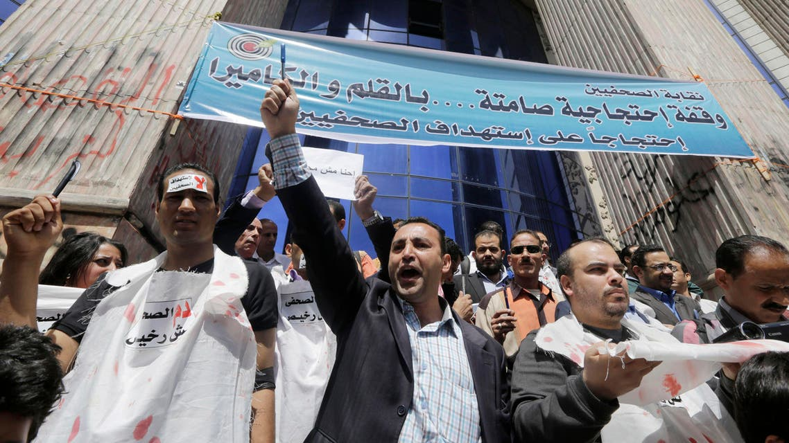 Egyptian journalists shout slogans as some wear symbolic white shrouds during a protest at the journalists syndicate in Cairo, Egypt, Thursday, April 17, 2014. AP