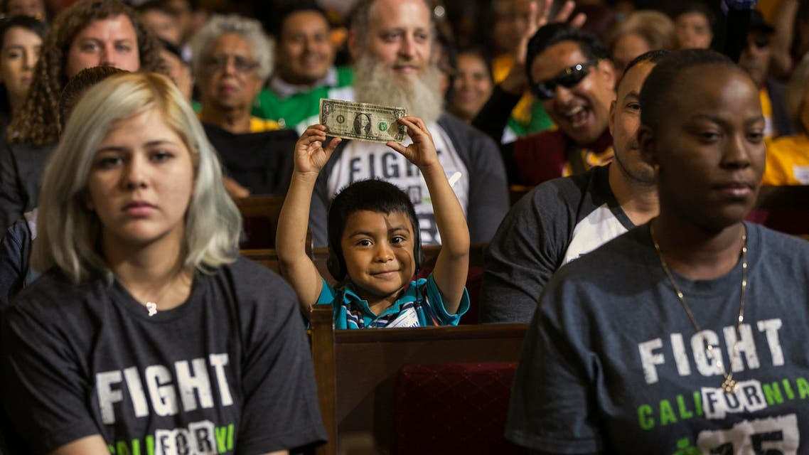David Lazo, 5, center, with his father Francisco, right, raises a dollar bill as workers await the Los Angeles City Council's vote to raise the minimum wage in the city to $15 an hour by 2020 in Los Angeles Wednesday, June 3, 2015.