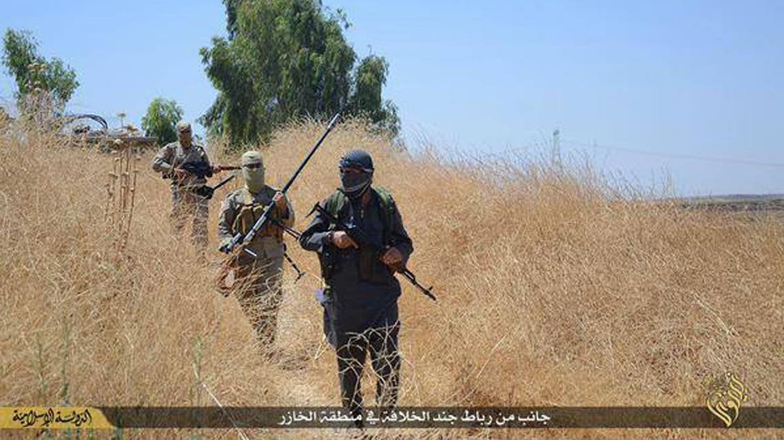 In this photo released on June 23, 2015, by a website of Islamic State militants, Islamic State militants patrol Khazer, Iraq, near Mosul. AP