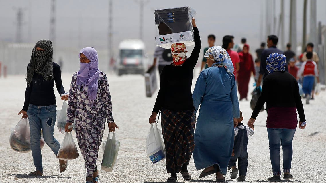Syrian refugees walk at a refugee camp in Suruc, on the Turkey-Syria border, Friday, June 19, 2015. (AP)