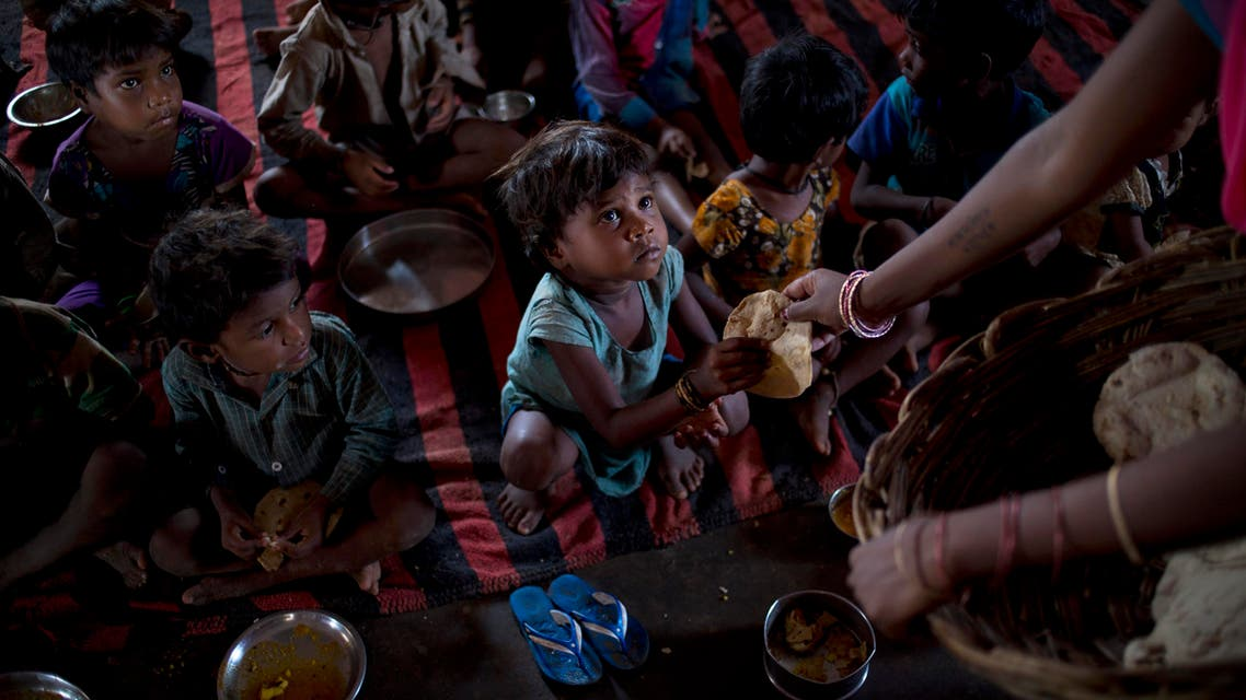 children have a meal of two flatbreads and a scoop of boiled potato curry at a government-run program serving lunch five days a week at Madkheda, Madhya Pradesh state, India. AP