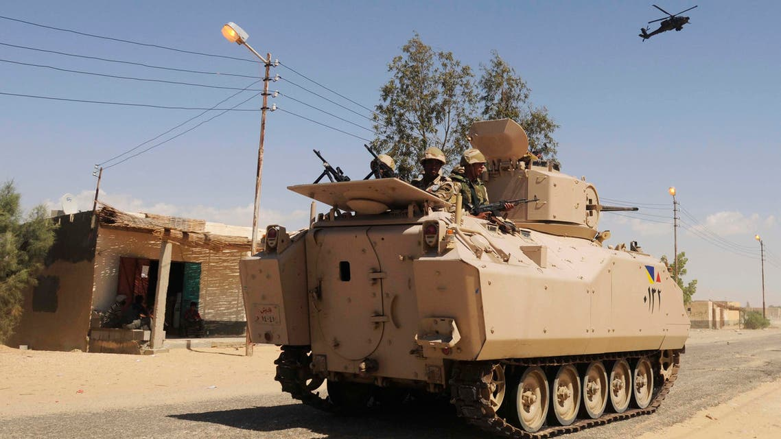 Egyptian Army soldiers patrol in an armored vehicle backed by a helicopter gunship during a sweep through villages in Sheikh Zuweyid, north Sinai, Egypt. AP