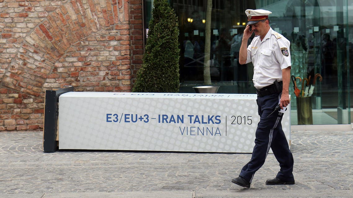 A Police officer walks past a fallen poster for the Iran talks in front of at Palais Coburg where closed-door nuclear talks with Iran take place in Vienna, Austria, Monday, July 6, 2015. (AP)