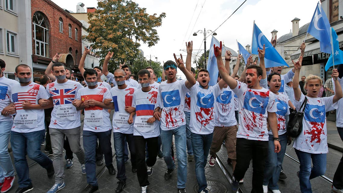 Uighurs living in Turkey and their supporters wear T-shirts with fake blood, representing Uighurs who have died in China's far-western Xinjiang Uighur region, during a protest in Istanbul, Saturday, July 4, 2015, against what they call as oppression by Chinese government to Muslim Uighurs in the province. Hundreds of people have marched in Istanbul to protest China over reports of its repression of its minority Muslim Uighur community. Turkey has ethnic and linguistic ties to the Uighurs, members of a Muslim ethnic minority in Xinjiang. Relations between China and Turkey have been strained over Turkish reports that Uighurs were banned from worshipping and fasting during the Muslim holy month of Ramadan. (AP Photo/Emrah Gurel)