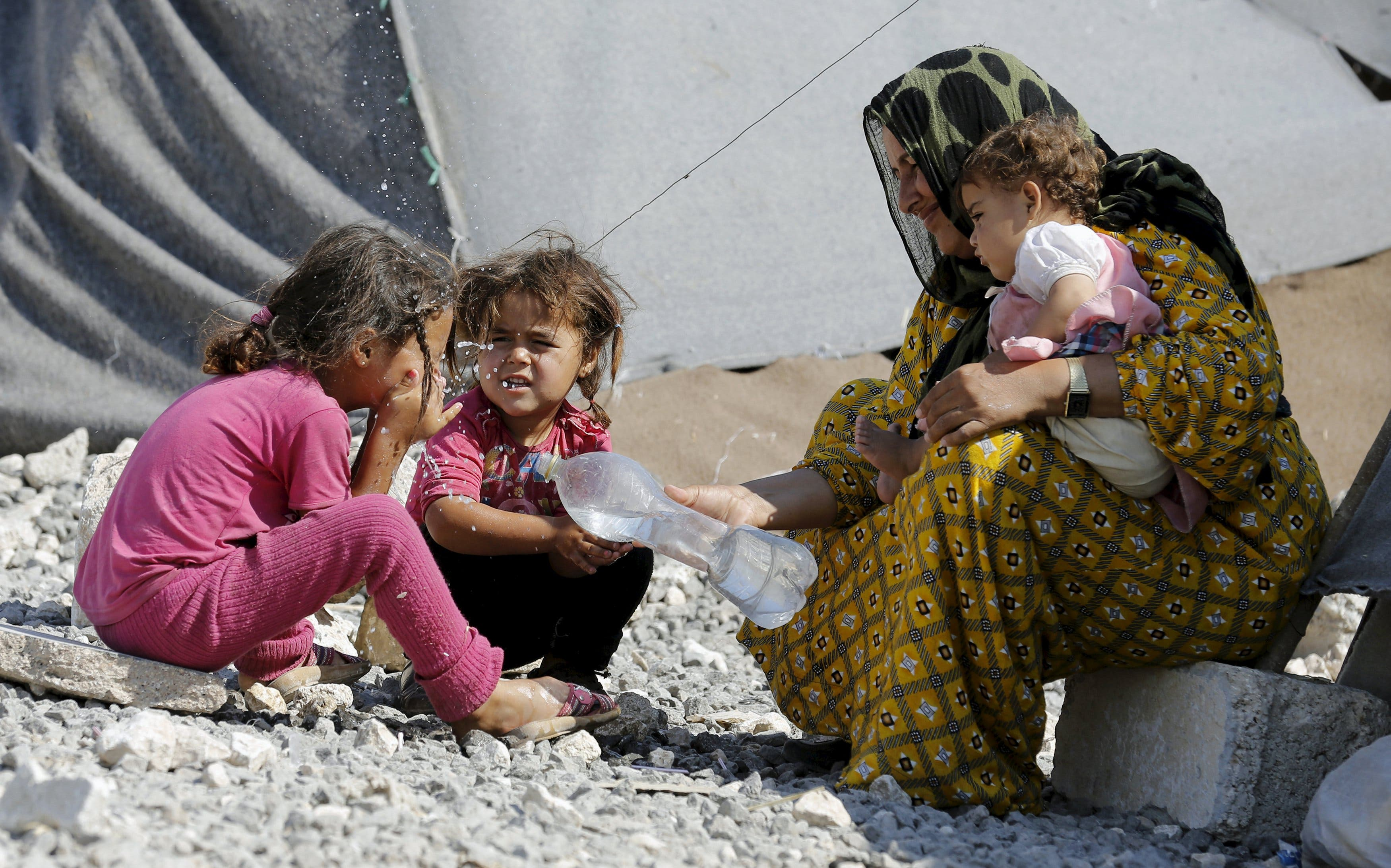 A Syrian refugee girl from the northern Syrian town of Tel Abyad washes her face as she is accompanied by her mother and sisters in Akcakale, in Sanliurfa province, Turkey, June 18, 2015. (Reuters)