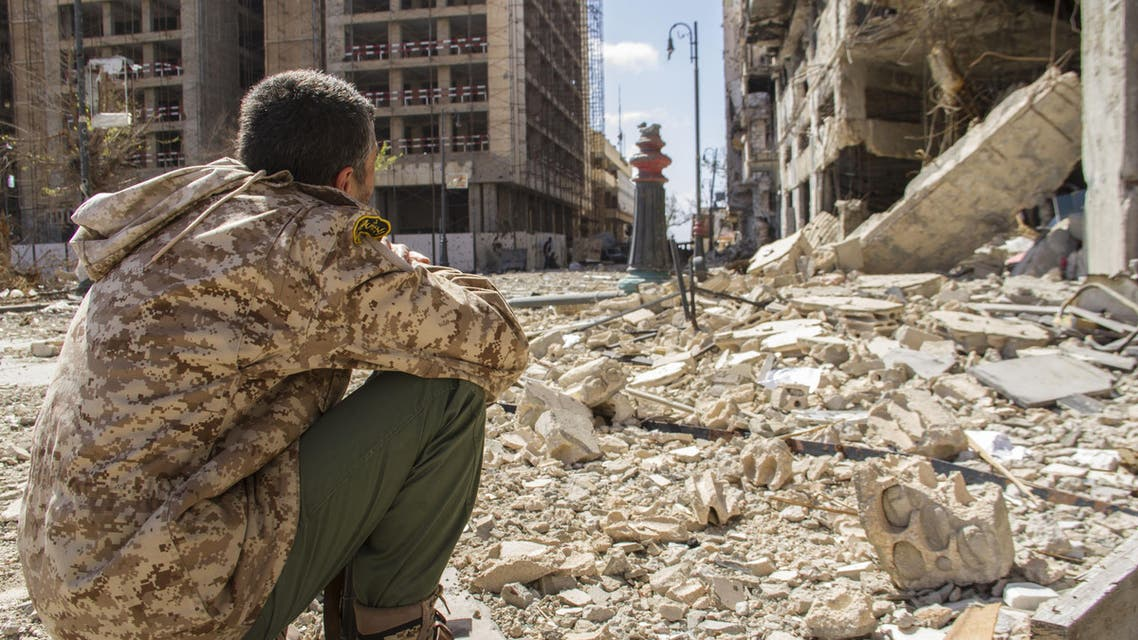 In this photo taken on April 4, 2015, a man looks on at the destruction on a street of the city of Benghazi, Libya. AP