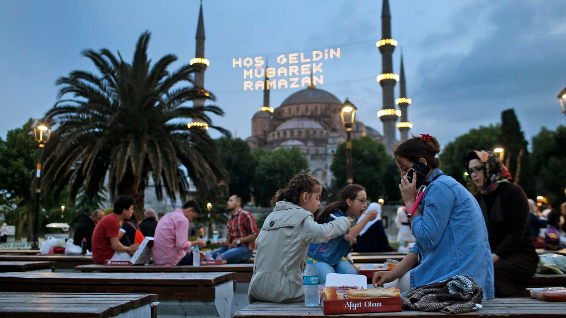 People break their fast backdroped by the the iconic Sultan Ahmed Mosque, better known as the Blue Mosque, decorated with lights marking the month of Ramadan, in the historic Sultanahmet district of Istanbul, Turkey, Thursday, June 18, 2015. AP