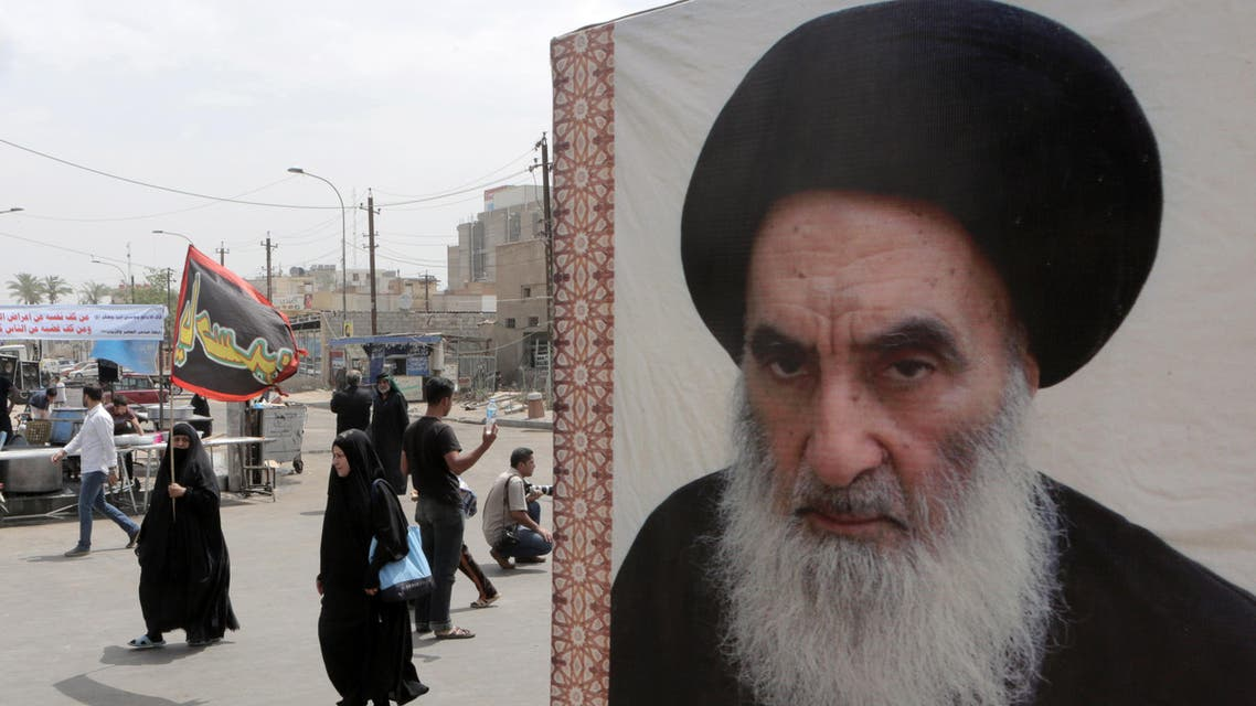 Shiite pilgrims make their way to the shrine of Imam Moussa al-Kadhim as passing by a poster of Shiite spiritual leader Grand Ayatollah Ali al-Sistani, right, in Baghdad, Iraq, Thursday, May 22, 2014. AP