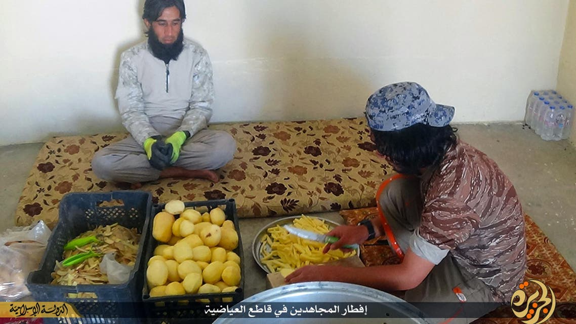 In this Sunday, June 28, 2015 photo provided by a website of the Islamic State group, IS members prepare meals, known as Iftar, for its members who fight on the front lines, in the northern Iraqi town of Ayadiyah, near Mosul. AP