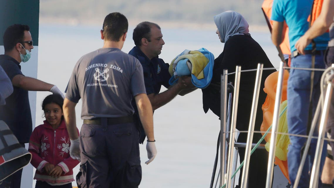 A mother gives her baby to a coast guard officer as she disembarks from a vessel at the port of Mitylene after being picked up by the Greek coast guard near the northeast Greek island of Lesvos on Wednesday, June 17, 2015. AP