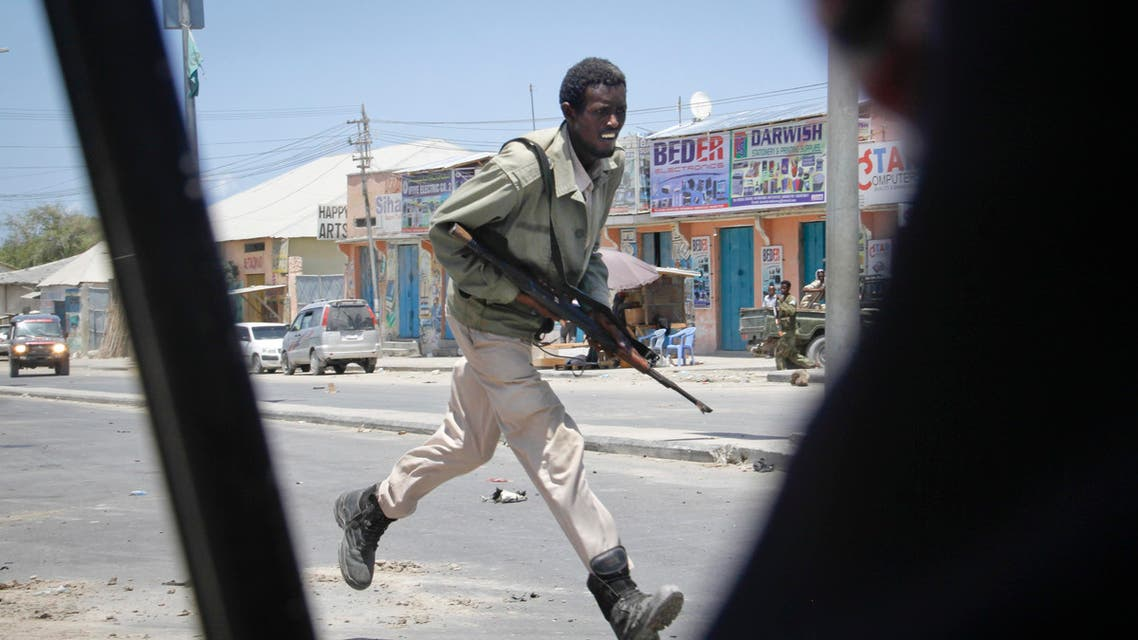 A Somali soldier runs during fighting following a car bomb that was detonated at the gates of a government office complex in the capital Mogadishu, Somalia Tuesday, April 14, 2015 AP